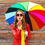 Fashion pretty woman with colorful umbrella sends air sweet kiss