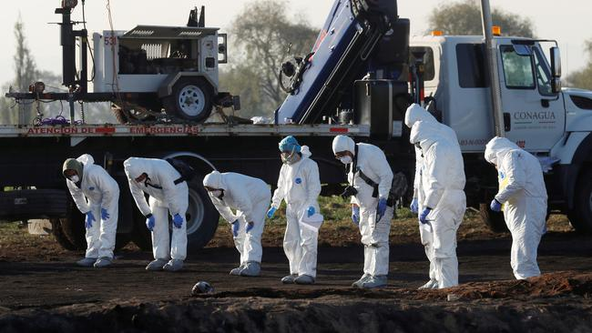 Forensic technicians work at the site where a fuel pipeline ruptured by suspected oil thieves exploded, in the municipality of Tlahuelilpan