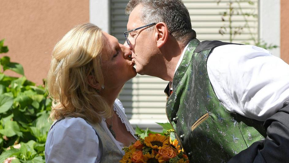 Austria's Foreign Minister Kneissl and her groom Meilinger kiss ahead of their wedding in Gamlitz