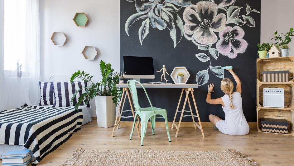 Woman drawing flowers on chalkboard wall in multifunctional home