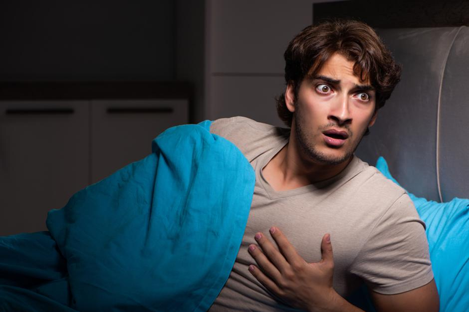 The young man scared in his bed having nightmares | Autor: Dreamstime