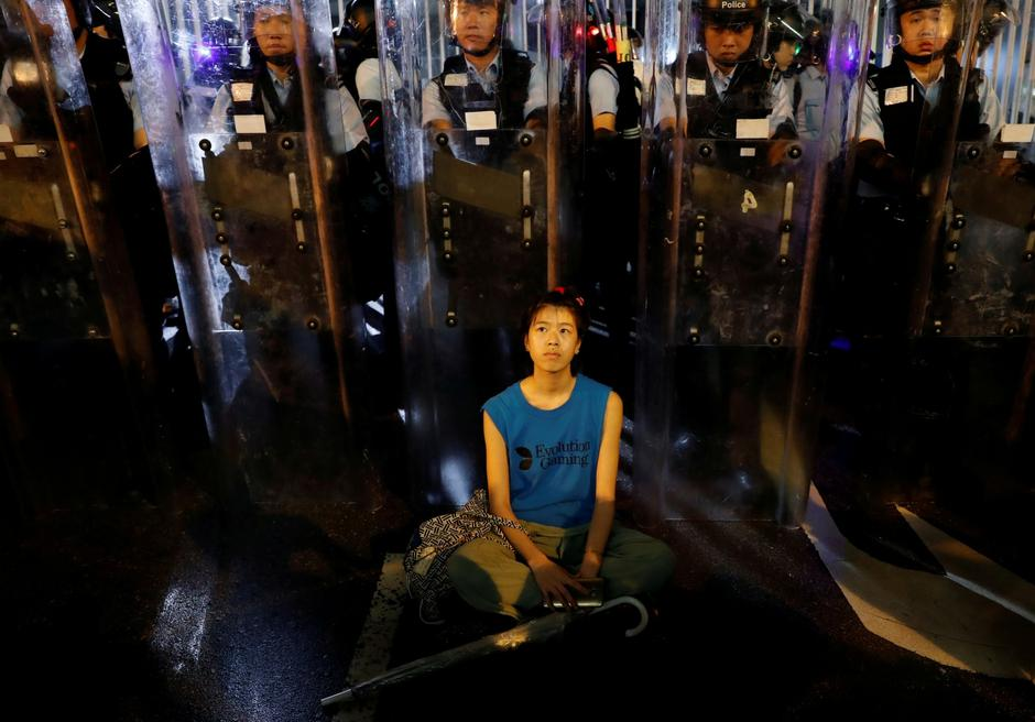 Demonstrator sits down in front of riot police during a demonstration to demand authorities scrap a proposed extradition bill with China, in Hong Kong | Autor: TYRONE SIU/REUTERS/PIXSELL/REUTERS/PIXSELL