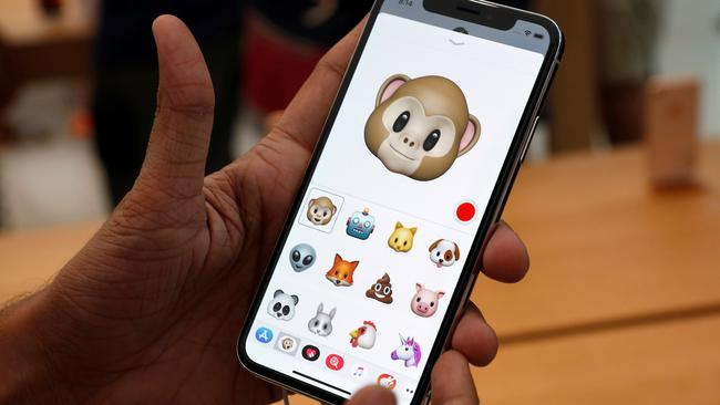 A man tries out the Animoji feature on the iPhone X during its launch at the Apple store in Singapore