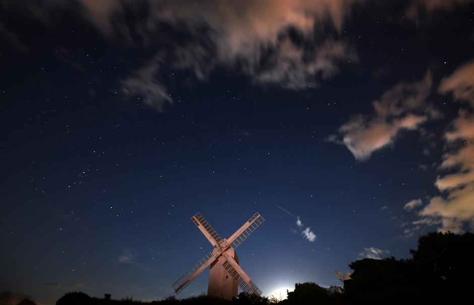 A meteor streaks past stars in the night sky above the Jill Windmill, during the Perseid meteor shower in Brighton | Autor: Hannah McKay/REUTERS