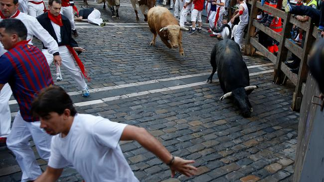 Runners sprint ahead of bulls during the first running of the bulls at the San Fermin festival in Pamplona