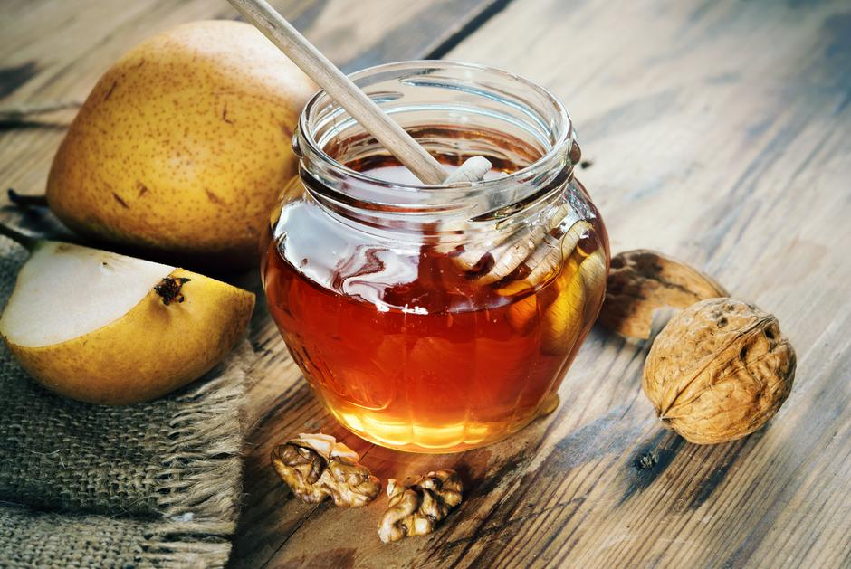 Jar of honey on a wooden table with walnuts and fruit | Autor: Anikaart
