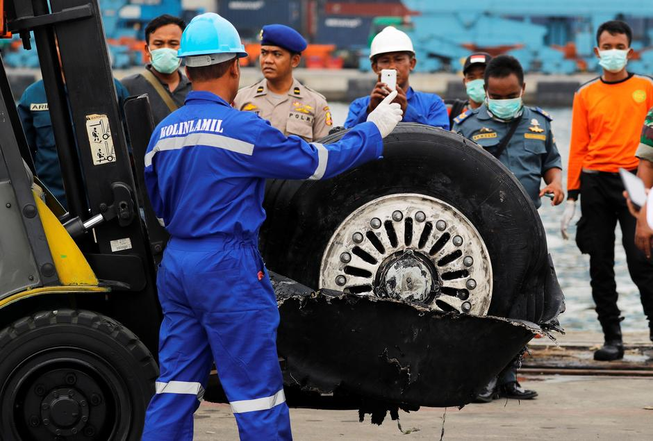 A worker assists his colleague during the lift up of a damaged tyre from the Lion Air flight JT610 jet, at Tanjung Priok port in Jakarta | Autor: BEAWIHARTA