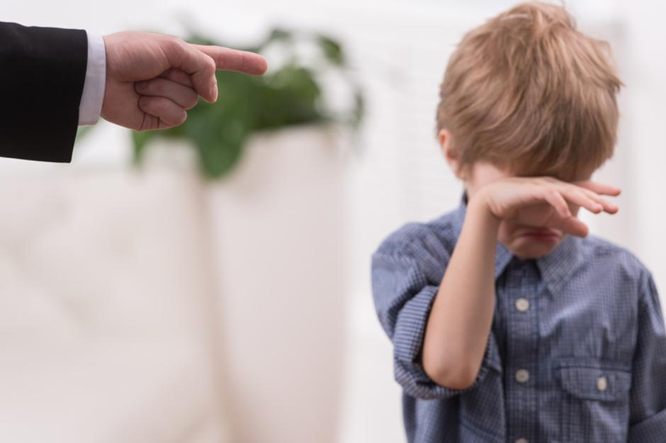 Strict father discipline naughty son. Isolated on white background boy wiping tears | Autor: Dreamstime