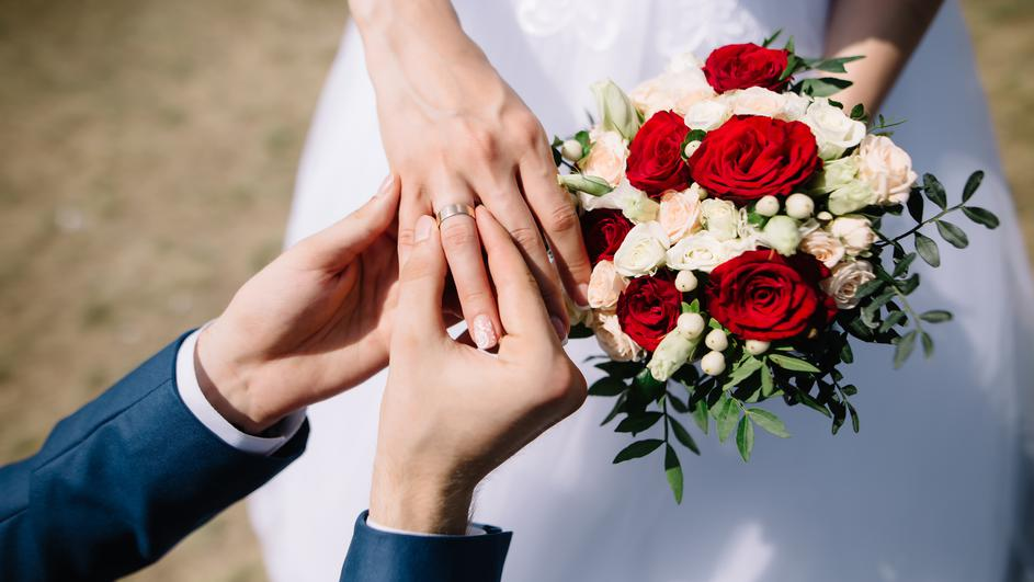 Love and marriage. Fine art rustic wedding ceremony outside. Groom putting golden ring on the bride's finger. Bouquet of red and white roses in hands