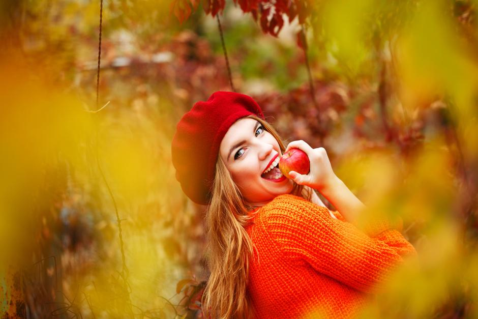 Lovely girl in beret and sweater, holding ripe apple and smiling | Autor: Vagengeim Elena