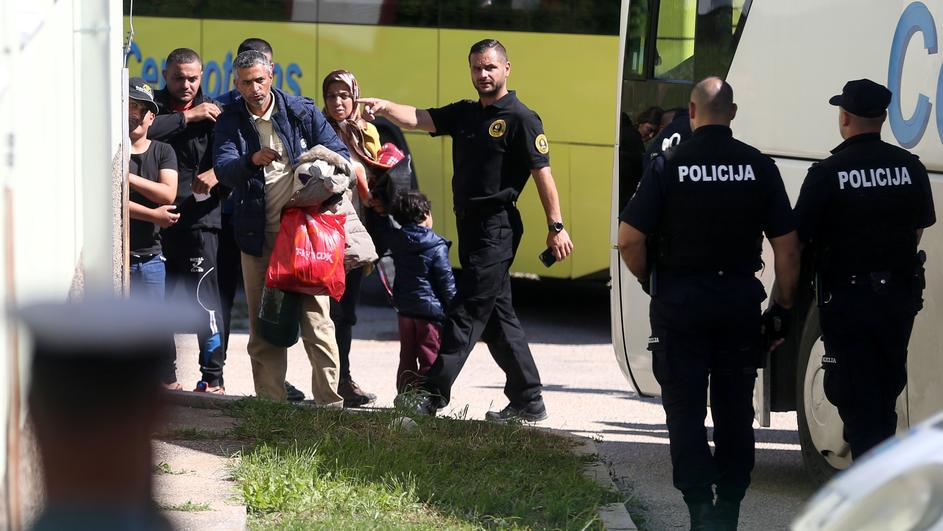 Migrants leave a bus at a camp in Salakovac