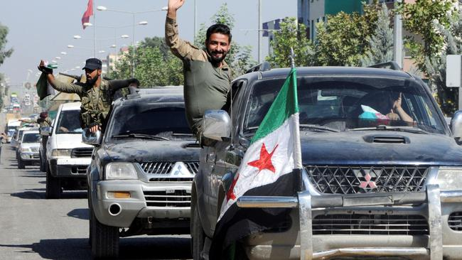 Members of Syrian National Army, known as Free Syrian Army, wave as they drive to cross into Syria in the Turkish border town of Akcakale