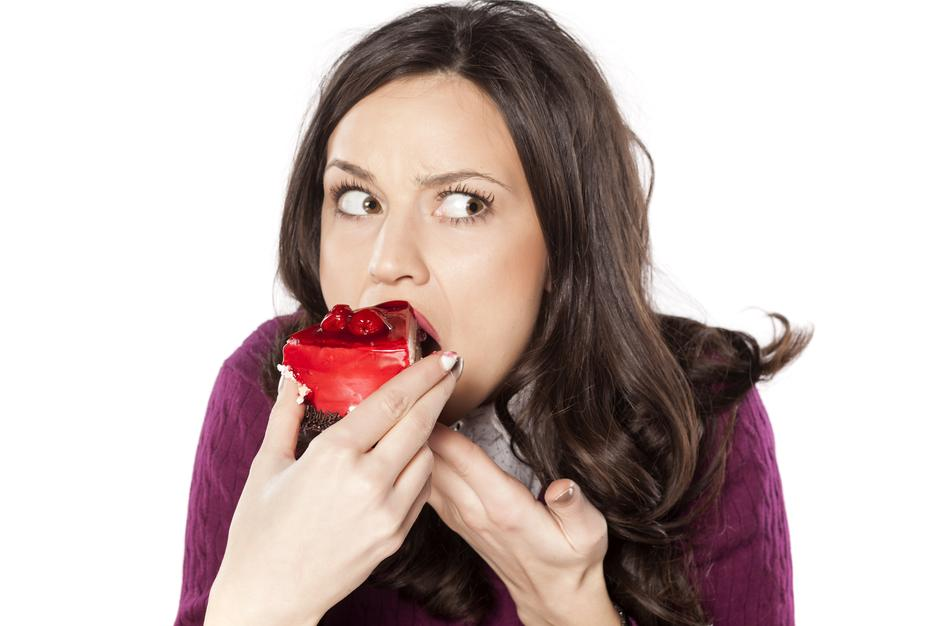 A woman eating a strawberry cake looking guilty | Autor: VladimirFLoyd