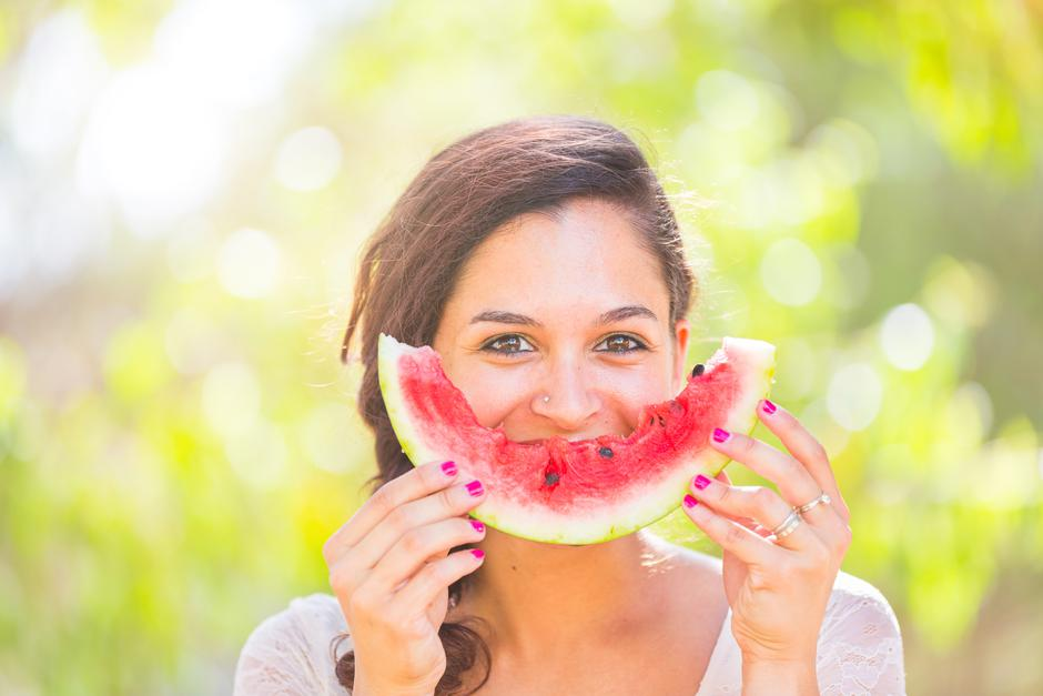 Beautiful young woman at park eating a slice of watermelon | Autor: William Perugini