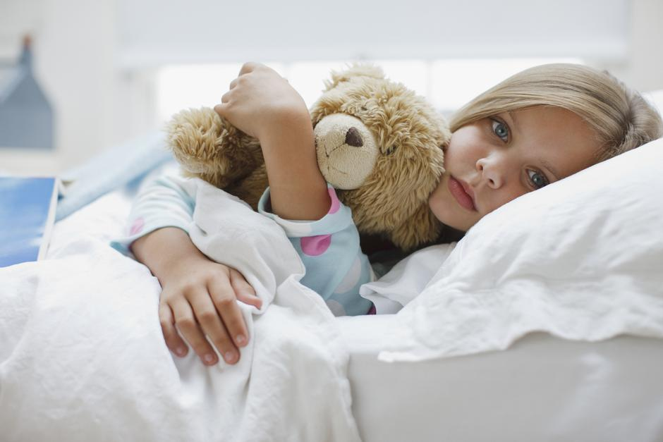Sick girl laying in bed with teddy bear | Autor: Tom Merton