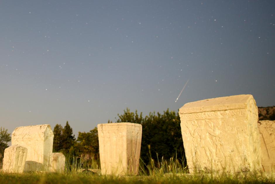A meteor streaks past stars in the night sky above medieval tombstones during the Perseid meteor shower in Radimlja near Stolac | Autor: DADO RUVIC