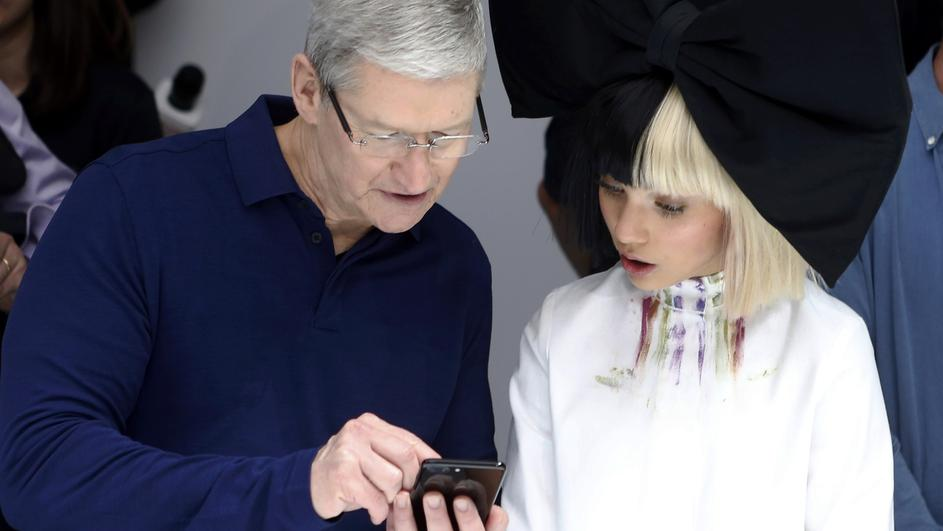 Tim Cook shows Maddie Ziegler an iPhone 7 during an Apple media event in San Francisco
