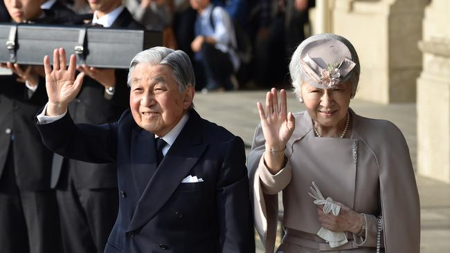 Japan's Emperor Akihito, accompanied by Empress Michiko, waves to well-wishers before leaving Ujiyamada Station after their visit to Ise Jingu shrine in Ise, Japan