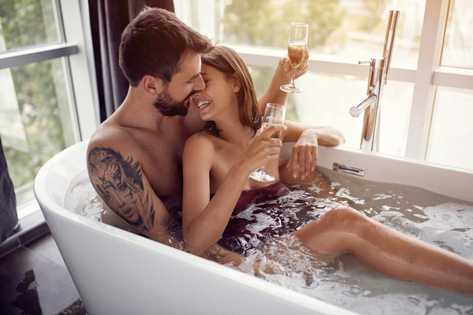 beautiful couple drinking champagne in the bathtub