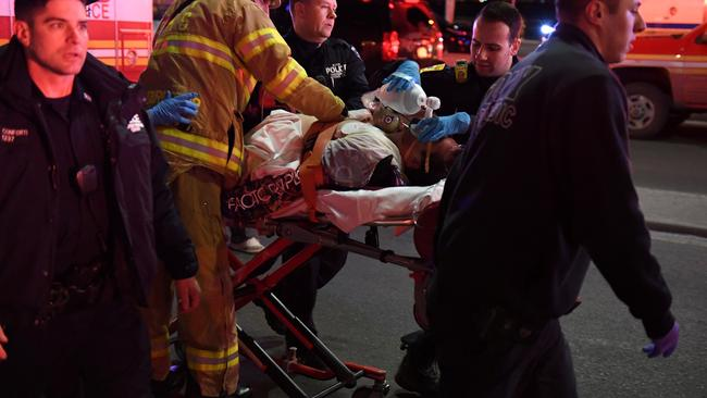 Paramedics and members of the FDNY perform CPR on a victim of a helicopter that crashed into the East River in New York