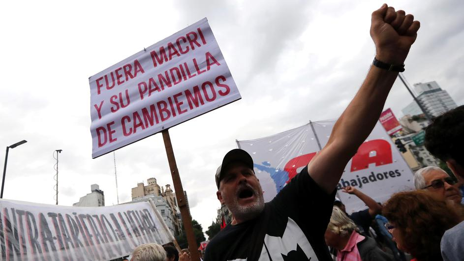 A man shouts slogans as he holds a sign during a protest against a cost increase in public and utility services in Buenos Aires