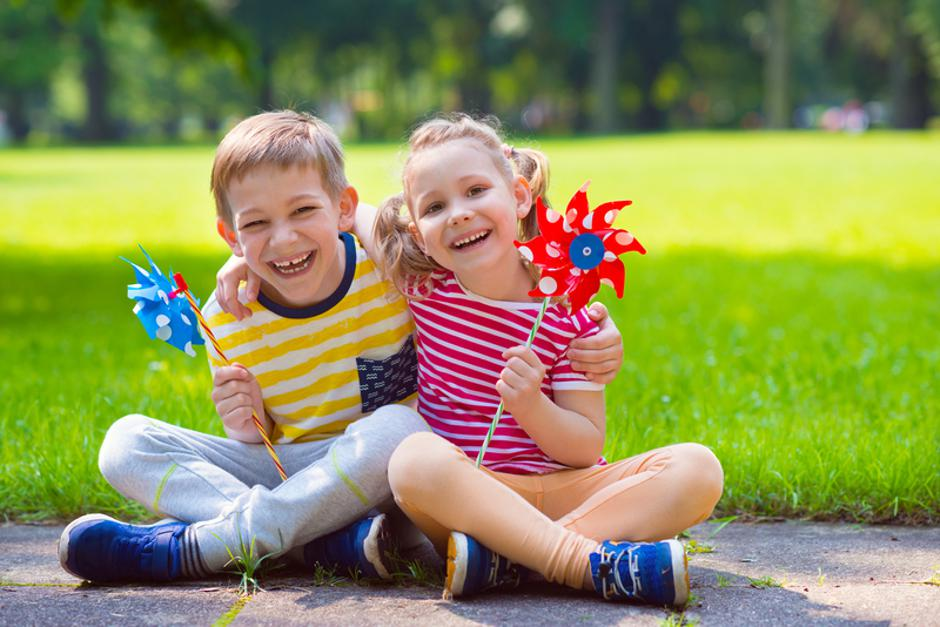 Two happy children playing with windmill | Autor: