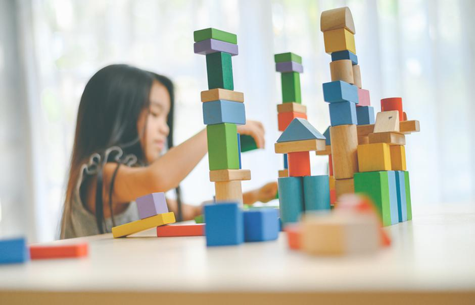 little girl  playing with construction toy blocks building a tow | Autor: Dreamstime