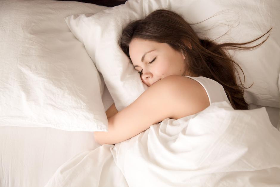 Woman sleeping in bed hugging soft white pillow | Autor: Dreamstime