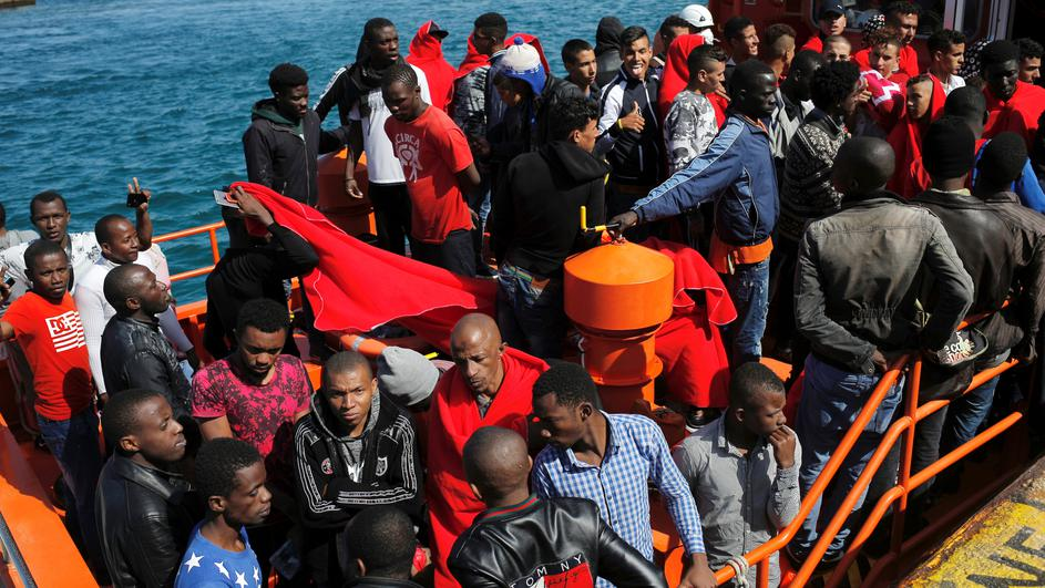 Migrants, intercepted aboard two dinghies off the coast in the Strait of Gibraltar, wait on a rescue boat to disembark after arriving at the port of Tarifa