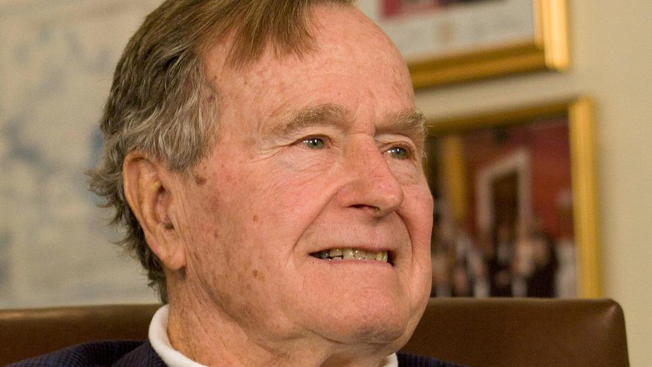 FILE PHOTO: Former President George H.W. Bush smiles as he listens to Republican presidential candidate Mitt Romney speak as he met with Bush to pick up his formal endorsement in Houston