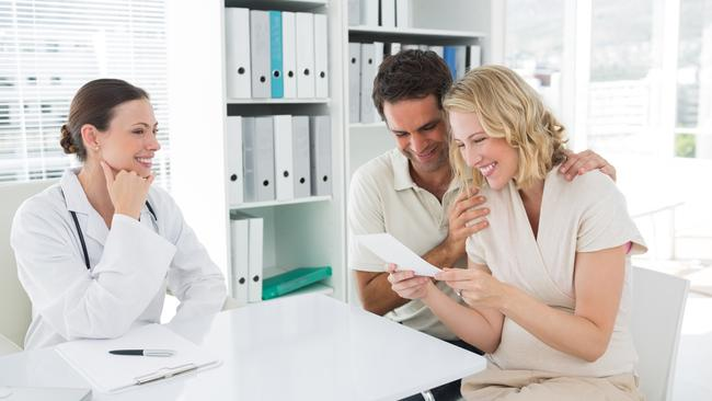Expectant couple looking at reports in clinic