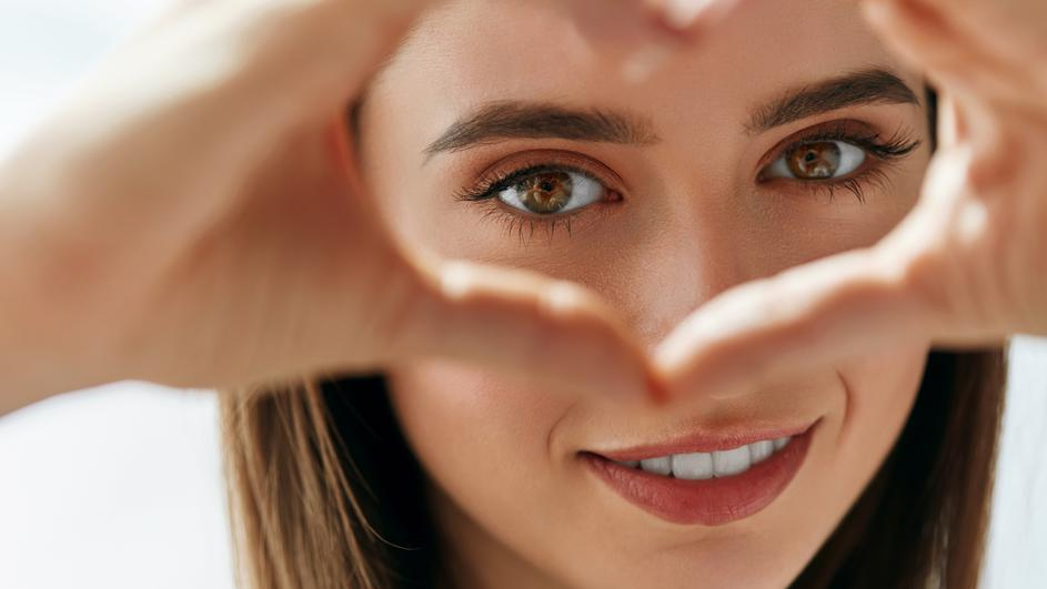 Beautiful Happy Woman Showing Love Sign Near Eyes.