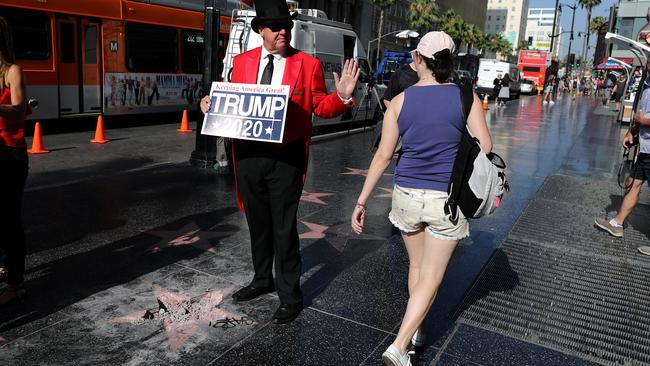 Greg Donovan, 58, waves at a woman walking on Hollywood Boulevard as he stands on President Donald Trump's vandalized star on the Hollywood Walk of Fame in Hollywood, Los Angeles