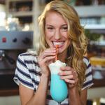 Portrait of woman drinking milkshake with a straw