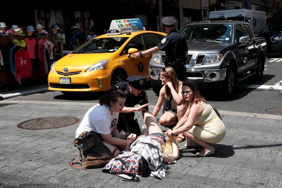 An injured woman is seen at a crosswalk in Times Square after a speeding vehicle struck pedestrians on the sidewalk in New York City | Autor: MIKE SEGAR