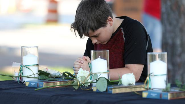 A young boy prays during a vigil held at the Texas First Bank after a shooting left several people dead at Santa Fe High School in Santa Fe, Texas