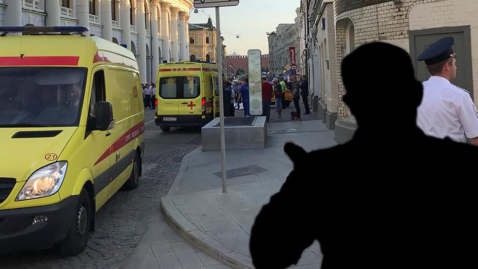 A police officer blocks the way as ambulances are parked near a damaged taxi, which ran into a crowd of people in central Moscow