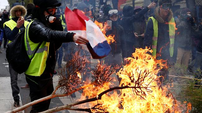 "A protester wearing a yellow vest burns a French flag at a barricade during clashes with police as part of a national day of protest by the ""yellow vests"" movement in Paris"