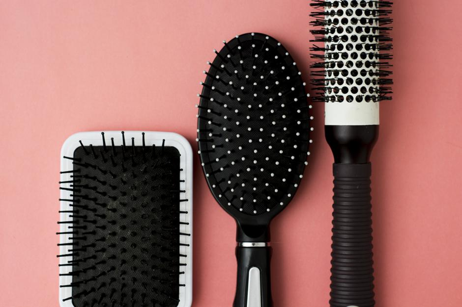 Used Hair brush tools on pink or coral background with copy space. Beauty fashion, hair care background. | Autor: Dreamstime