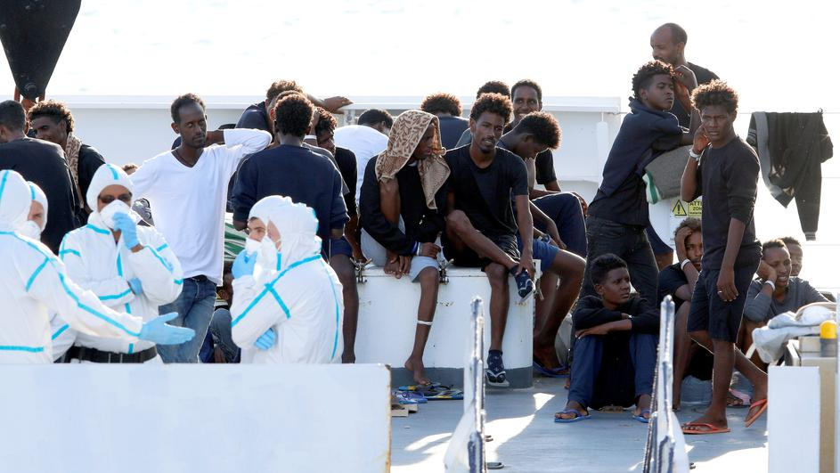 "FILE PHOTO: Migrants wait to disembark from the Italian coast guard vessel ""Diciotti"" at the port of Catania"