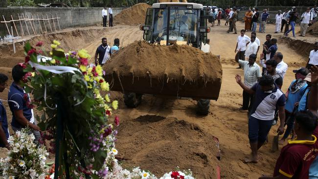 Men coordinate a mass burial of victims at a cemetery near St. Sebastian Church in Negombo