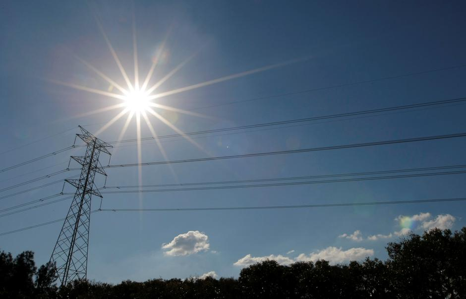 FILE PHOTO: Sun shines over a high tension power line in an industrial area of Sydney | Autor: Tim Wimborne