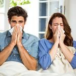 Young couple blowing their nose in tissue