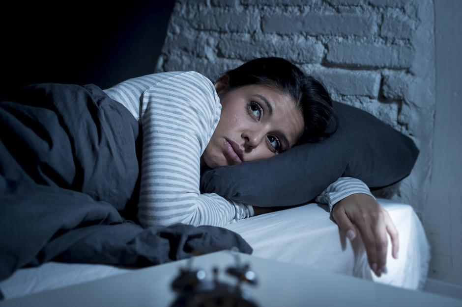 woman in bed late night trying to sleep suffering insomnia | Autor: OcusFocus