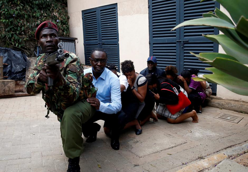People are evacuated by a member of security forces at the scene where explosions and gunshots were heard at the Dusit hotel compound, in Nairobi | Autor: BAZ RATNER
