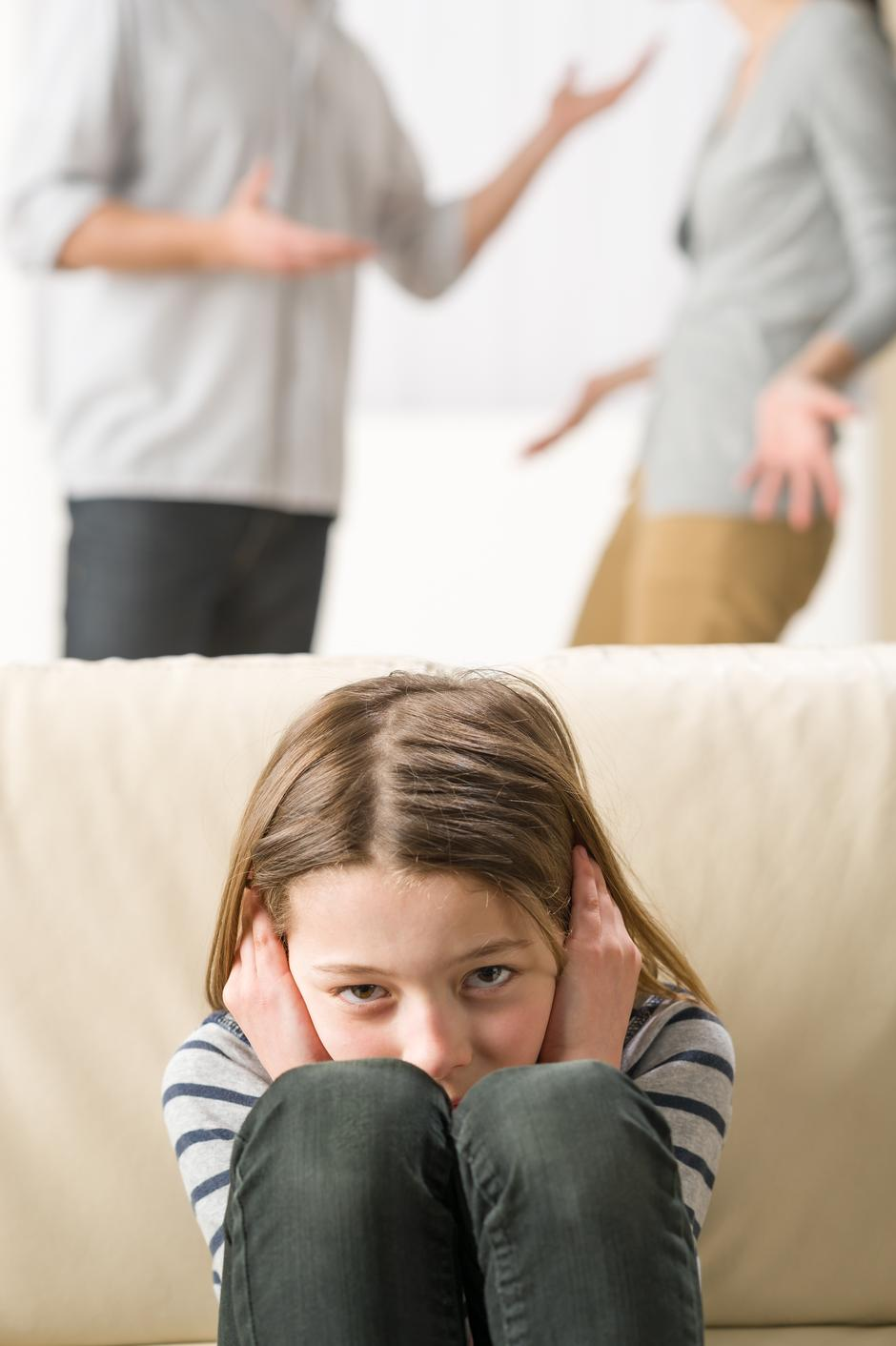 Little girl is troubled because parents arguing | Autor: J.M. Guyon - Copyright 2013