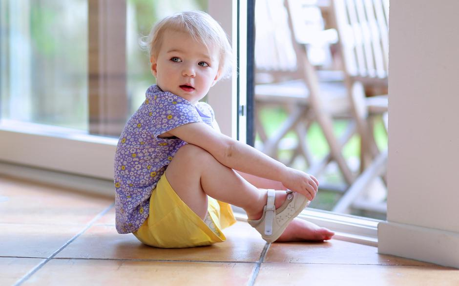 Toddler girl putting shoes sitting on floor next to window | Autor: CroMary