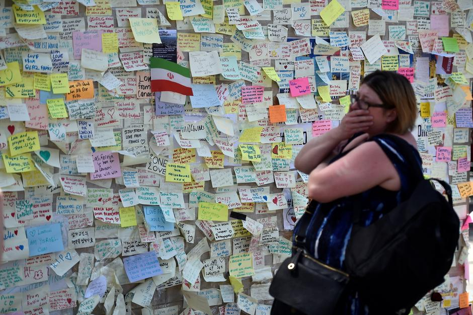 A woman reacts in front of a wall of messages in Borough Market, which officially re-opened today following the recent attack, in central London | Autor: Hannah McKay/REUTERS