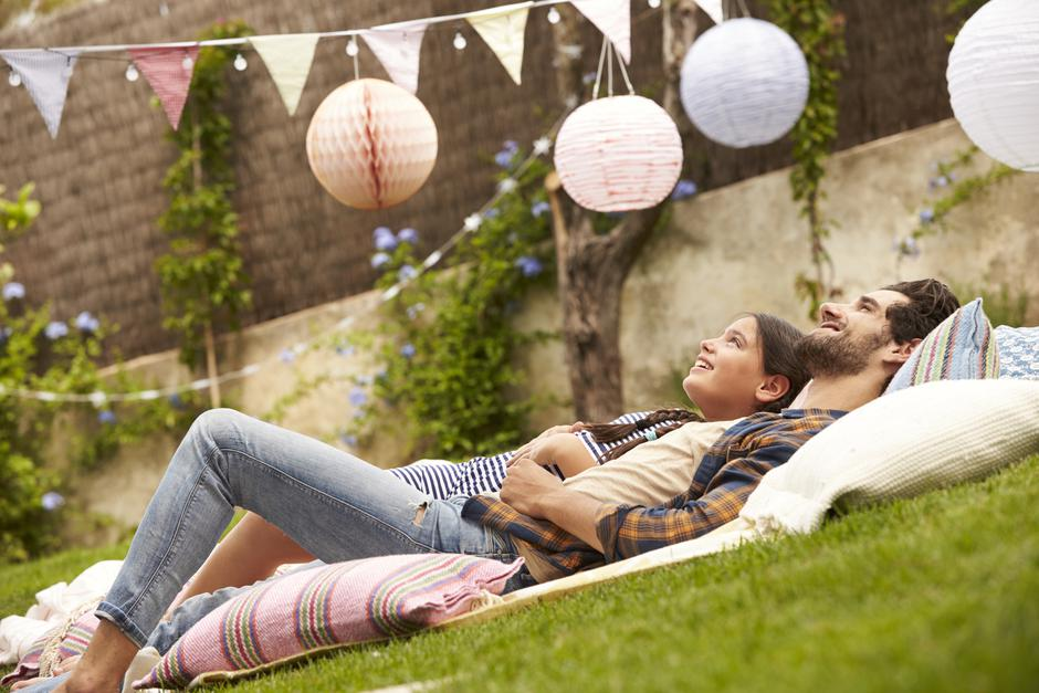 Father With Daughter Relaxing On Rug In Garden Together | Autor: monkeybusinessimages