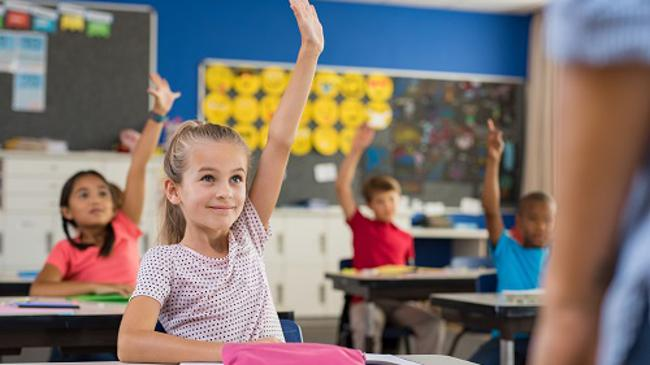 Children raising hands in classroom